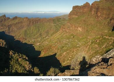 The tourtous road that descends to the Masca ravine (canyon), Tenerife island, Canary Islands, Spain. La Palma island at the horizon.