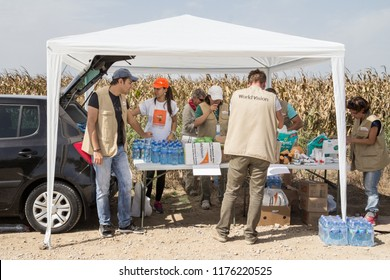TOVARNIK, CROATIA - SEPTEMBER 19, 2015: Workers of the NGO World Vision provinding aid to refugees at the border between Serbia and Croatia, on the Balkans Route, during the Refugees Crisis