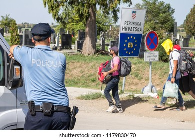 TOVARNIK, CROATIA - SEPTEMBER 19, 2015: Croatian police officer looking at Refugees passing in front of the EU entrance sign on the Serbia-Croatia border crossing of Sid Tovarnik during Refugee Crisis