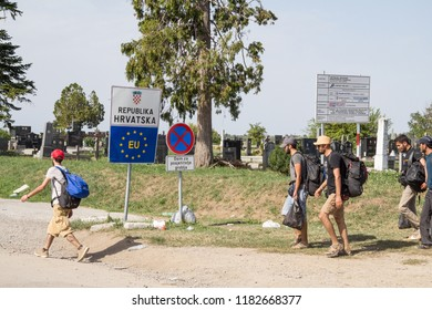 TOVARNIK, CROATIA - SEPTEMBER 19, 2015: Refugees passing in front of the EU entrance sign in front of the Serbia-Croatia border crossing of Sid Tovarnik on the Balkans Route, during the Refugee Crisis