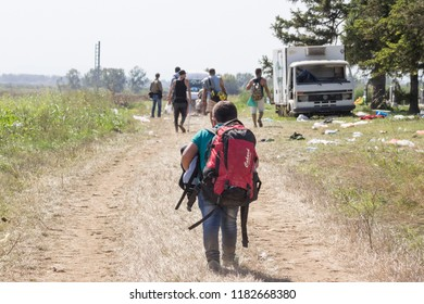 TOVARNIK, CROATIA - SEPTEMBER 19, 2015: Young refugee child carrying heavy backpack on the Croatia Serbia border, between cities of Sid  & Tovarnik on the Balkans Route, during the Refugee Crisis
