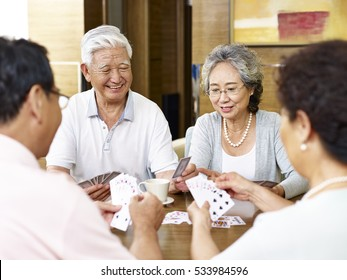 tow senior asian couples playing cards together
