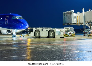 The tow tractor rolls back the passenger airplane from the air bridge at the night airport apron