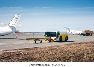 Tow tractor with towbar and tank truck aircraft refuelers moves at the airport apron