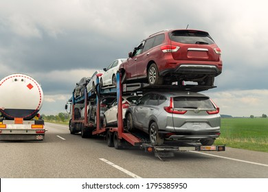 Tow truck car carrier semi trailer on highway carrying batch of damaged cars sold on insurance car auctions for repair and recovery. Vehicles shipment and rescue service