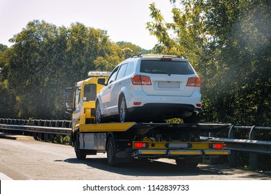 Tow truck with a car on the road