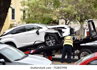 A tow truck driver loading a wrecked car onto a tow truck
