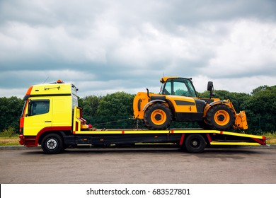 The tow truck on the platform transports the new tractor, the equipment for technical and agricultural works.