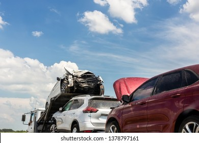 Tow truck trailer on highway carrying three damaged cars sold on insurance car auctions for repair and recovery.  Vehicles shipment and rescue service