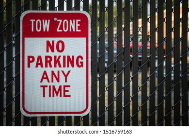 Tow Zone No Parking sign on black fence warns people away from parking lot