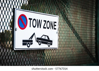 Tow Zone sign on a steel grid gate