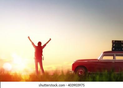 Toward adventure! Girl relaxing and enjoying road trip. Beautiful young woman rejoices dawn.
