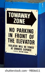 """a """"Towaway Zone"""" """"no parking in front of the elevator"""" sign"""