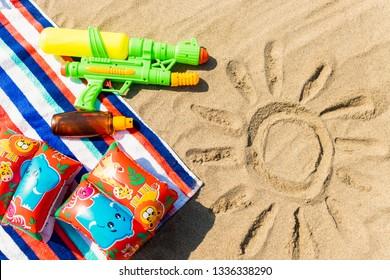 Towel, floats, water gun and sunscreen on the beach