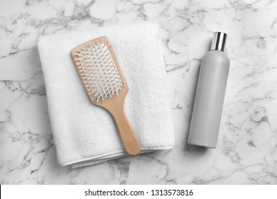 Towel, hair brush and shampoo on marble background, top view