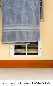 Towel hanging in front of in-wall electric baseboard heater heating unit. Dangerous house home fire hazards.
