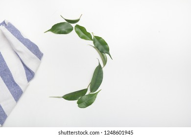 Towel and leaves on a white background. Copy space
