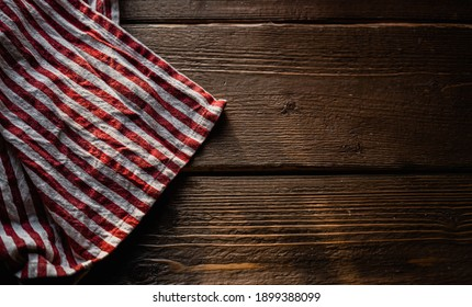 a towel made of red and white striped fabric, lying on a table made of wood with a texture, daylight falls from the window. copy space