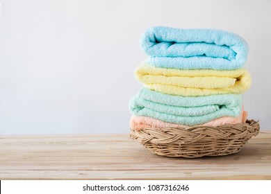 towel on basket on wood table with white wall and copy space, can be used for present products