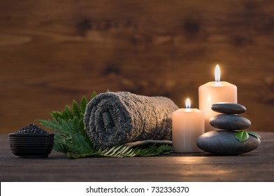 Towel on fern with candles and black hot stone on wooden background. Hot stone massage setting lit by candles. Massage therapy for one person with candle light. Beauty spa treatment and relax concept.