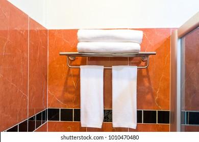 Towel on stainless steel shelf in bathroom