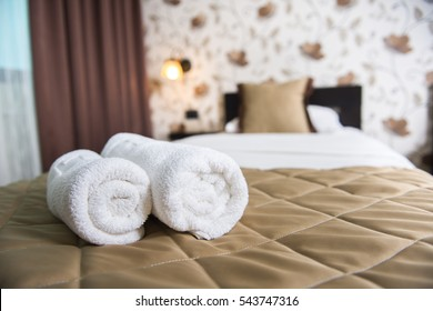 Towel rolls on a hotel bed.