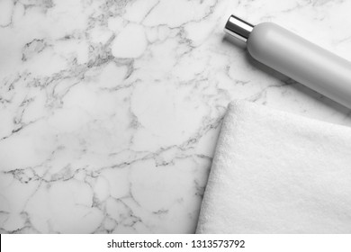 Towel and shampoo on marble background, top view with space for text