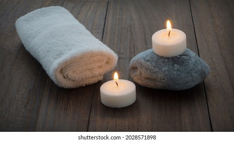 towel, stone and candles on the wooden table. Spa style.