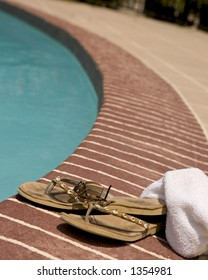 Towel, sun glasses and worn flip-flops laying beside a pool