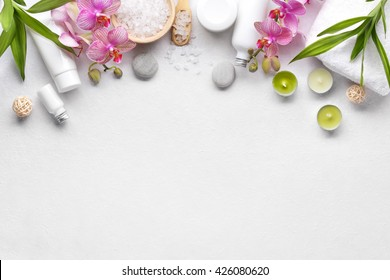 Toallas, flores de orquídea, hojas de bambú y cosméticos