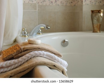 Towels and a bar of soap on the side of a large tub with the faucet and a vase blurred in the background