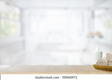 Towels in basket on top wood table  with blurred bath room interior Background. For product display montage.