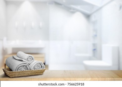Towels in basket on wood top table with copy space on blurred bathroom background. For product display montage.
