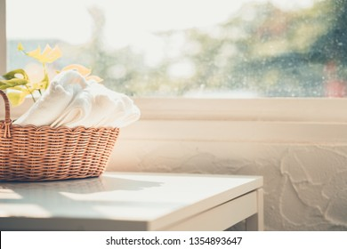 Towels in basket on wooden table over defocused living background