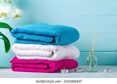 Towels, a branch of an orchid, an aroma sticks and a candles on a blue background. Spa. Hygiene. Aroma therapy
