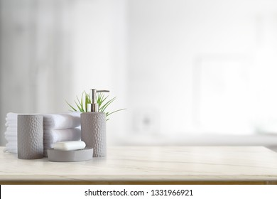 Towels and ceramics shampoo or soap on top marble table with copy space on blurred bathroom background.