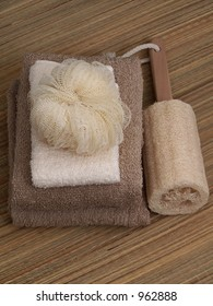 Towels folded, sea sponge and scrubby on natural straw mat.