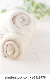 Towels and green ivy on white tile