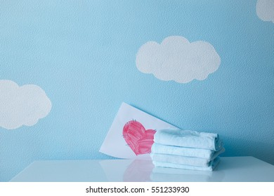 towels and heart on the table on blue sky background