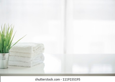 Towels and houseplant on white table with copy space. For product display montage.