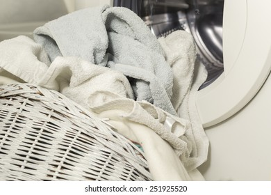Towels in the laundry basket in front of the washing machine