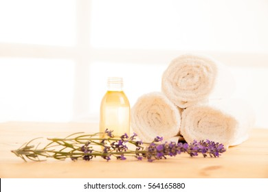 Towels lavender and massage oil on a table in spa salon