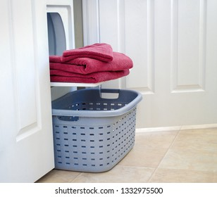Towels lying on dyer door above laundry basket.
