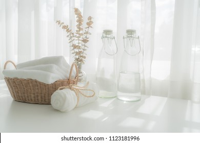Towels on basket, water bottle with copy space blurred bathroom background. For product display montage.