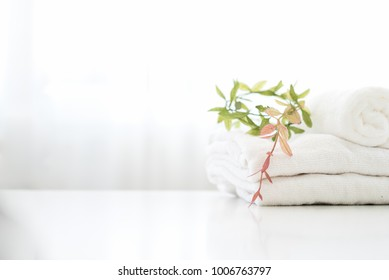 Towels on top white wood table with copy space on blurred bathroom background. Products Display Concept.