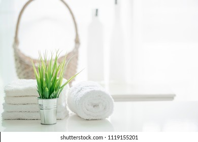 Towels on white table with copy space on blurred bathroom background. For product display montage.