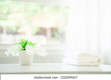Towels on white top table with copy space on blurred bathroom background. For product display montage