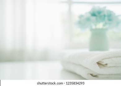 Towels on white wood top table with copy space on blurred bathroom background. For product display montage.