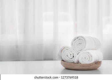 Towels on wood plate with copy space blurred bathroom background. For product display montage
