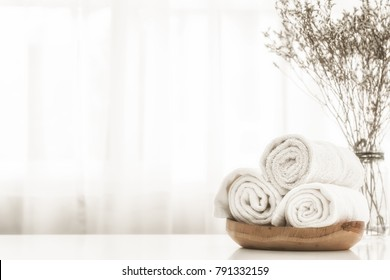 Towels on wood plate with copy space blurred bathroom background. For product display montage.